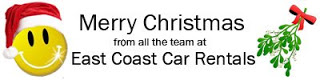 Merry Christmas From All the Team at East Coast Car Rentals with a Smiley Face and Santa Hat