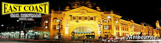 Flinders Street Railway Station Melbourne Victoria at Night with East Coast Car Rentals Logo and Melbourne Text