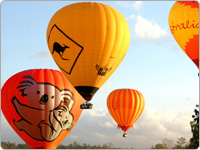 Four Orange Hot Air Balloons Floating in the Sky
