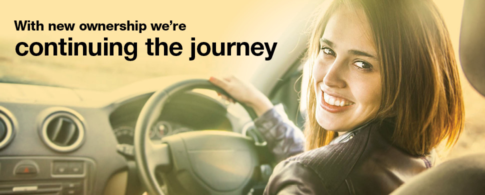 Woman Driving Car and Looking Back Smiling to Celebrate New Company Ownership