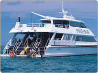 Poseidon Snorkel & Dive Agincourt Ribbon Reefs Cruise Vessel with Snorkellers Disembarking from the Back of the Boat