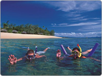 Two People Snorkelling the Great Barrier Reef Next to an Island as Part of Shaolin Low Isles Port Douglas Reef Tours