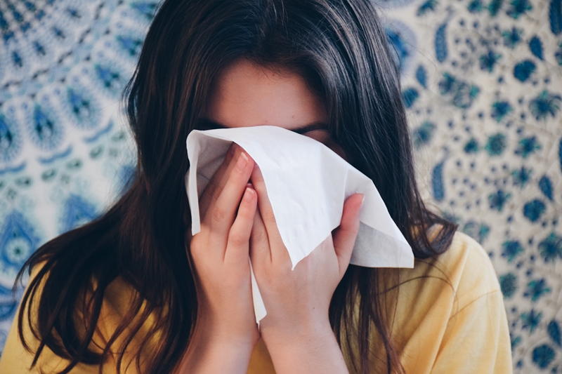 Girl using facial tissue to blow her nose