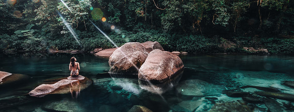 Woman Sitting on Rock in Natural Pool at Babinda Boulders Cairns in Far North Queensland
